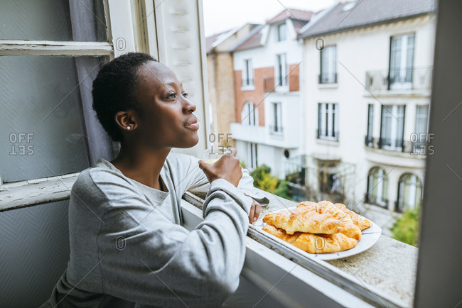 Young woman enjoying view from window while having breakfast