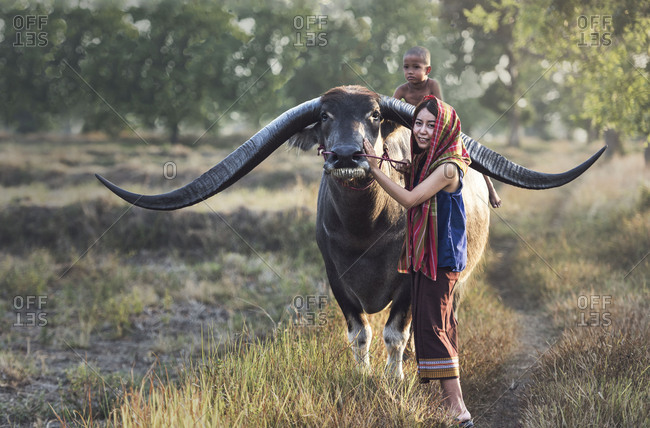 Asian woman (Thai) farmer with a buffalo in the field