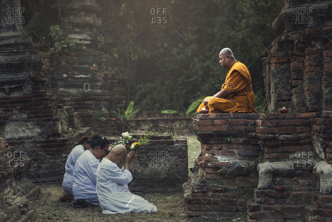 Ayutthaya, Thailand - February 22, 2016: People praying respect to monk on Ayutthaya. Roughly 95% of the Thai people are practitioners of Theravada Buddhism, the official religion of Thailand
