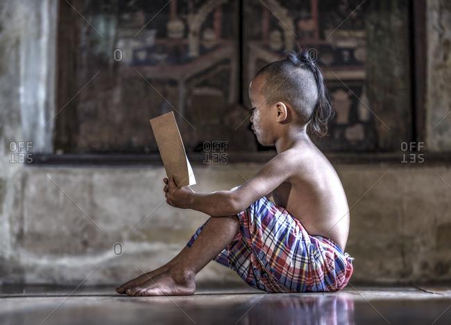 Asian boy reading book