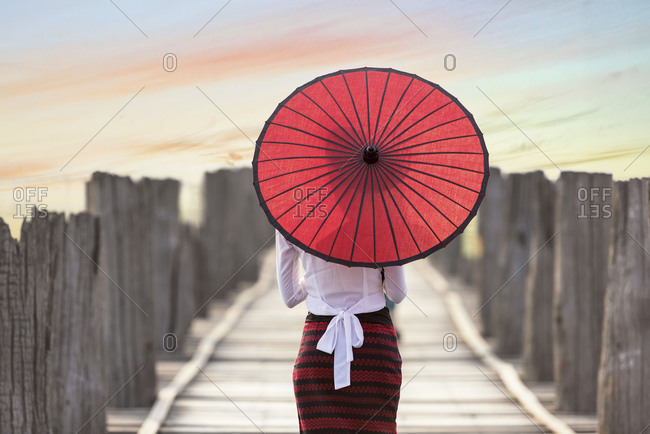 Burmese woman holding traditional red umbrella and walking on U Bein Bridge, Mandalay, Myanmar