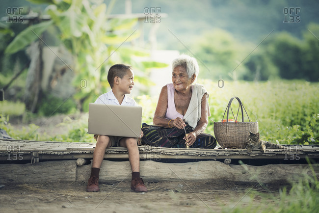Happy boy and grandmother using laptop