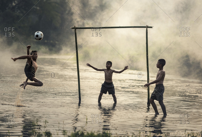 Boy kicking a soccer ball in the river