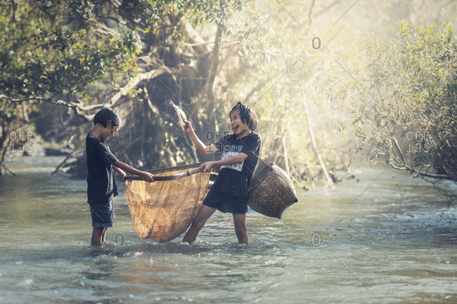 Asian children fishing at the creek