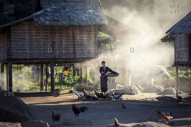 Asian girls feeding chickens at Laos countryside, Laos