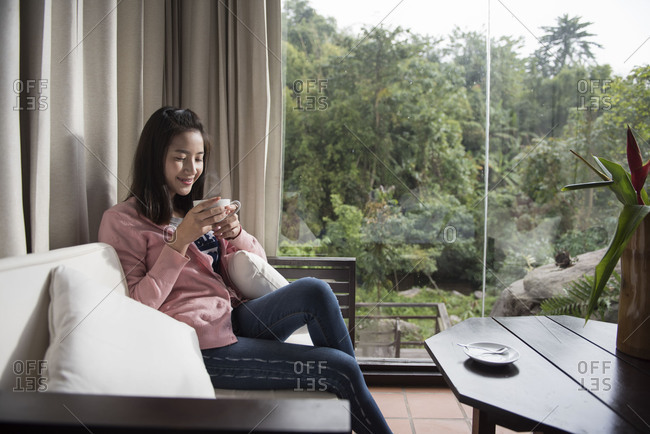 Woman drinking coffee or tea and thinking at home
