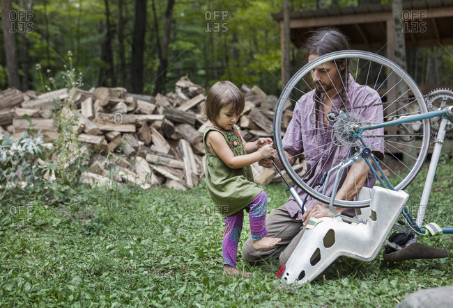 Man looking at daughter pumping bicycle tier in backyard