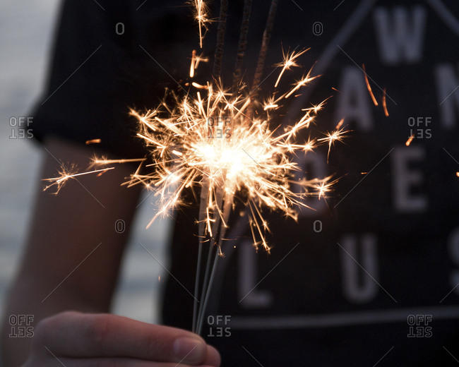 Midsection of woman burning sparklers