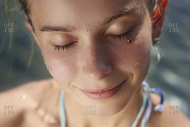Close-up of lady bug on woman face
