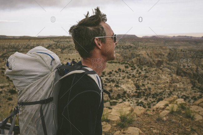 Side view of hiker looking away while carrying backpack against semi-arid landscape
