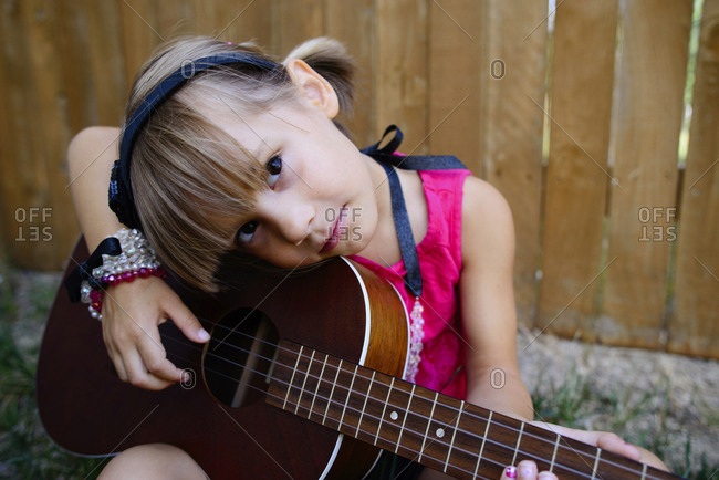 Portrait of girl strumming guitar while sitting against wooden fence