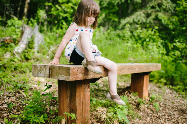 Girl in polka dot shirt sitting on bench next to woods
