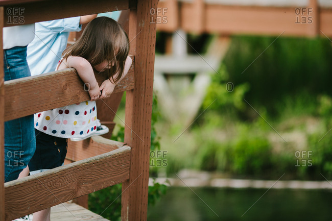 Cute little girl looks down into lake on wooden boardwalk