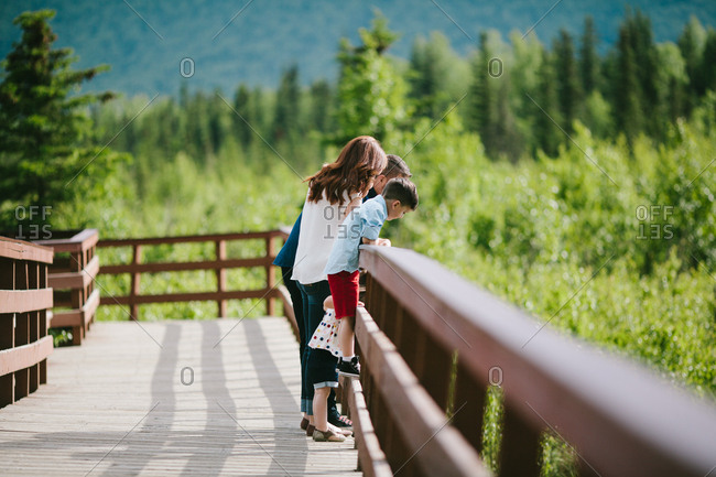 Side view of happy family standing on bridge against forest