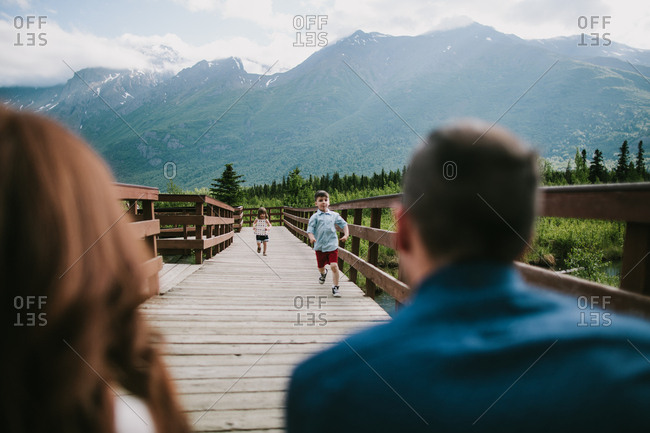 Children running on bridge to parents