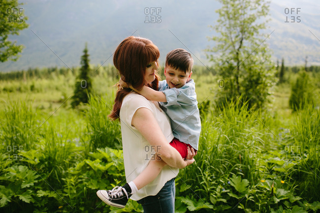 Happy mother holding her young boy in a meadow