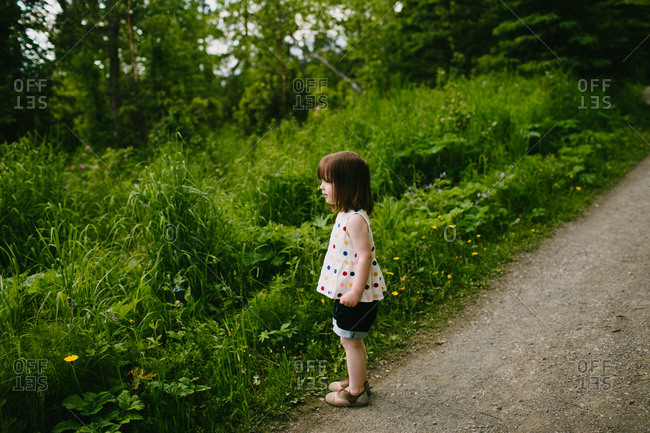 Young girl in polka dot shirt standing on nature trail