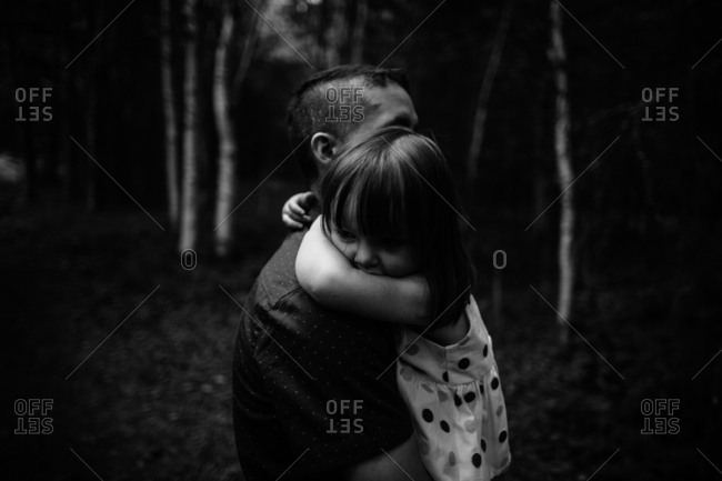 Father and daughter hugging on a trail