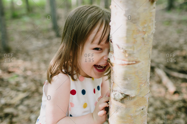 Close up of girl in polka dot shirt laughing against a tree in forest