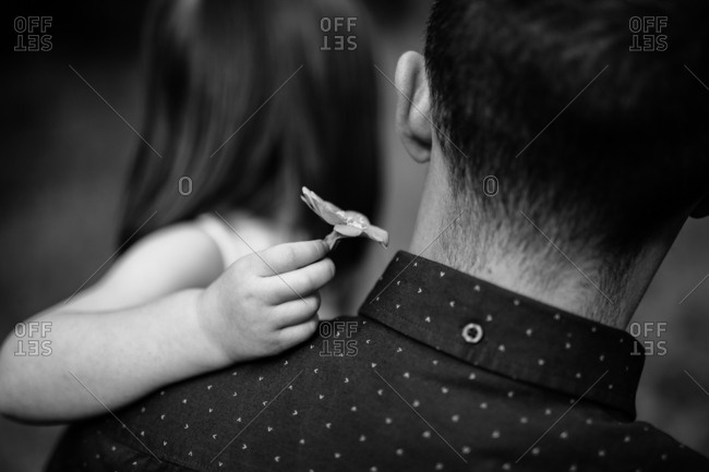 Father and girl holding a flower