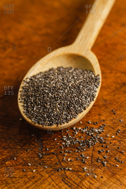 Wooden spoon full of chia seeds on table