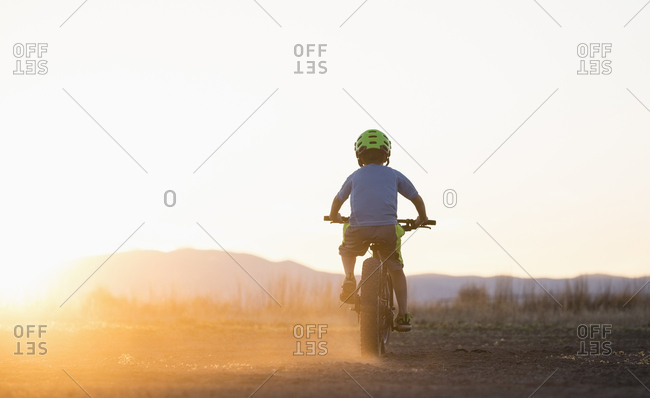 USA, Colorado, Rear view of boy (8-9) cycling at sunset