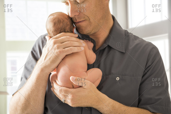 Father embracing newborn son (0-1 month)