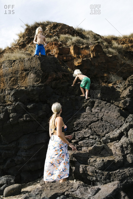 USA, Hawaii, Kauai, Mother with sons (4-5, 8-9) climbing on rocks