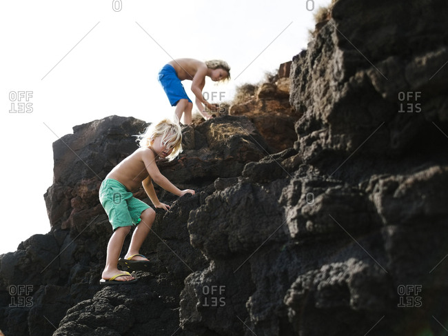 USA, Hawaii, Kauai, Boys (4-5, 8-9) climbing on rocks