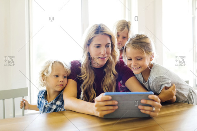 Mother and children (4-5, 6-7, 8-9) with digital tablet