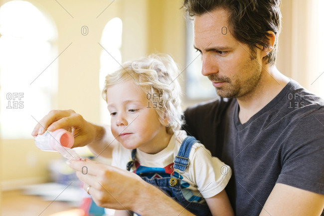 Father applying medicine to son (4-5)