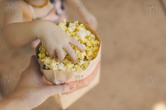 Child reaching for popcorn in bag