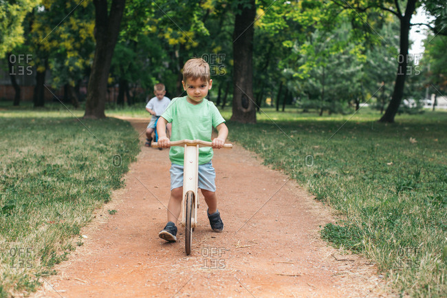 Boy riding balance bike on dirt path in the park