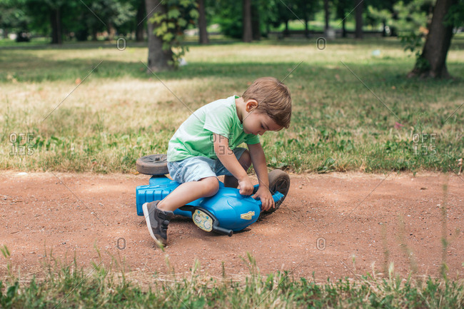 Boy playing with toy tricycle on dirt path in park