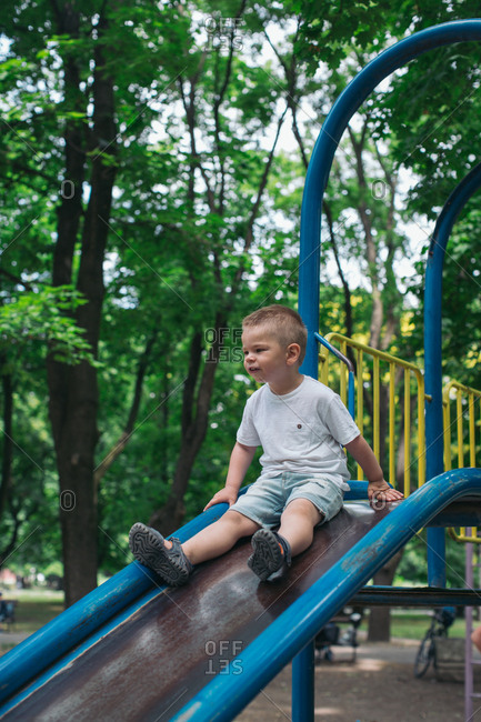 Boy on top of slide at playground