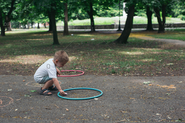 Boy drawing with sidewalk chalk at park
