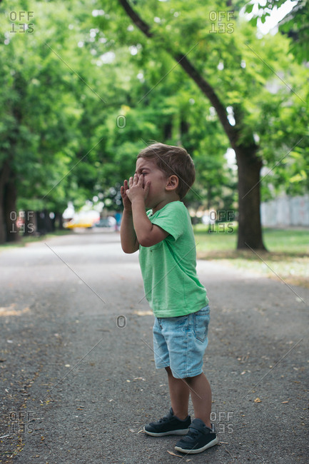 Little boy with hands on face standing in middle of road