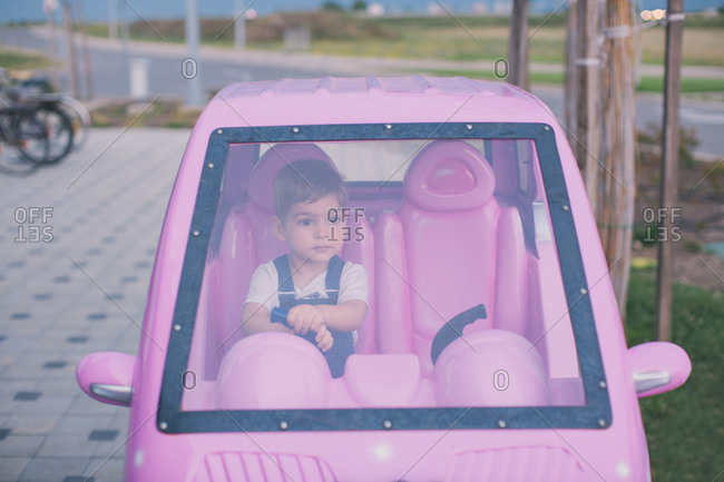 Little boy sitting in pink toy car
