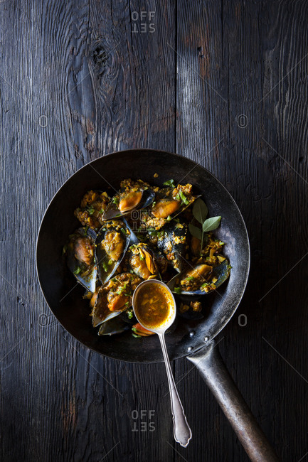 Seafood masala in a wok on a dark wood table