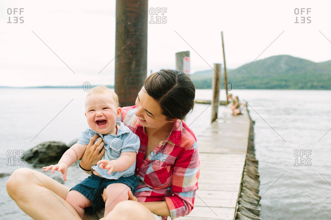 Woman holding happy baby on pier