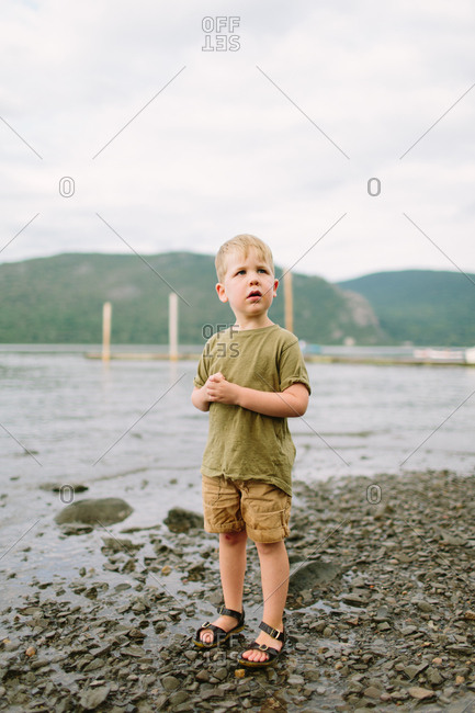 Little boy standing at water's edge