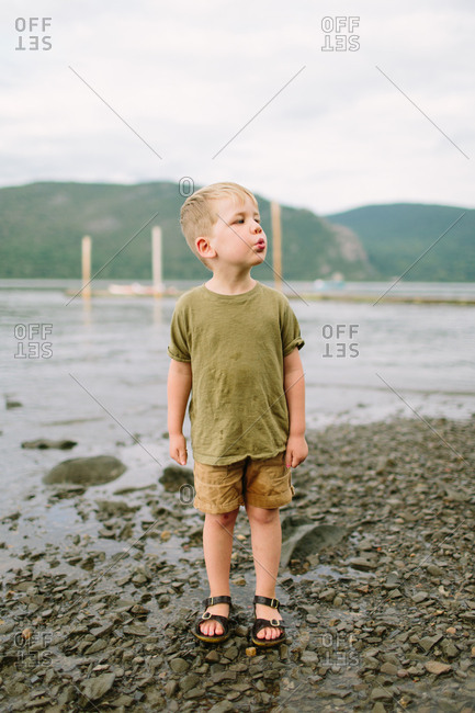 Little boy whistling at water's edge