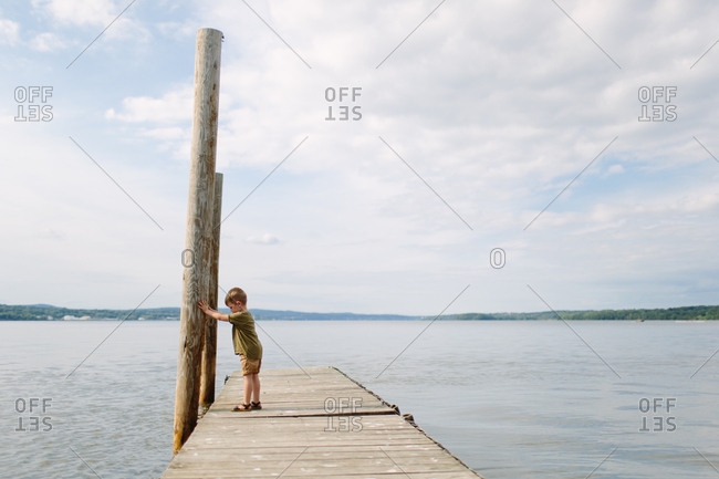 Young boy next to pole on pier