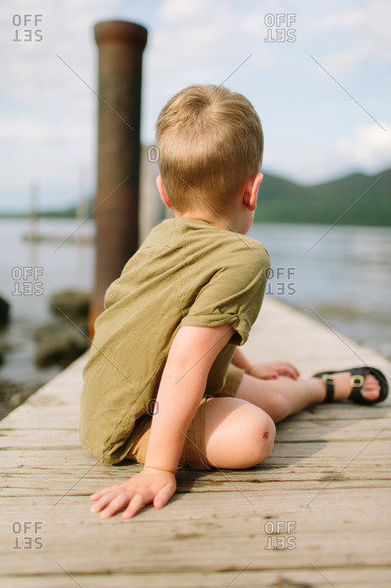 Young boy sitting on a pier