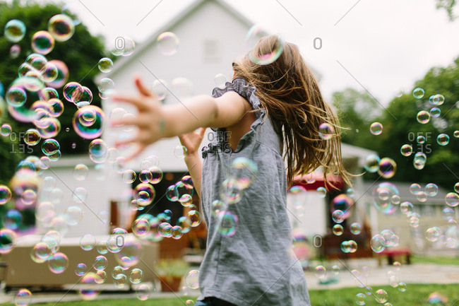 Girl running through a yard filled with soap bubbles