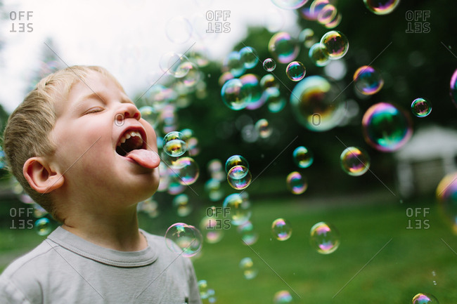 Young boy trying to catch bubbles in his mouth