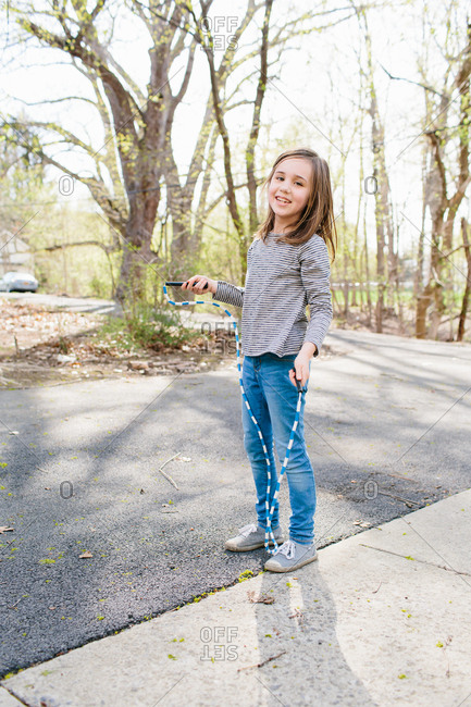 Girl with jump rope in driveway