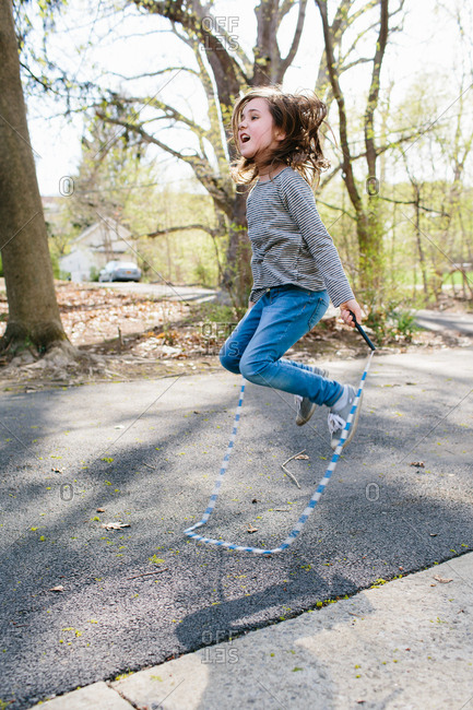 Young girl jumping rope in driveway