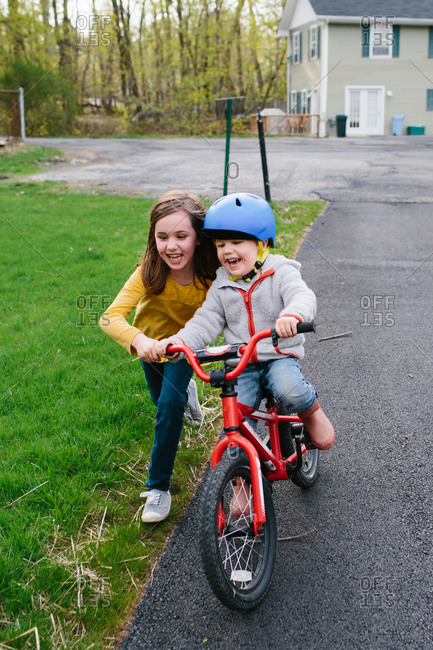 Girl helping her younger brother learn to ride a bike