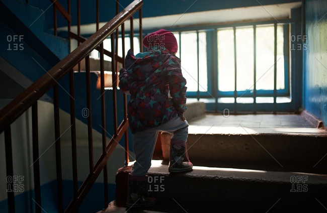 Child moving up the old stairs in Khrushchevka building. Khrushchevka is a Post-Stalin period housing typology built in USSR in the 60s and 70s as a scaled down versions of Stalinist buildings, with smaller apartments and plain brick facades